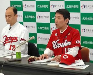 カープのユニホーム姿で記者会見する広島労働局の河合智則局長(右)=26日、広島市、木村和規撮影