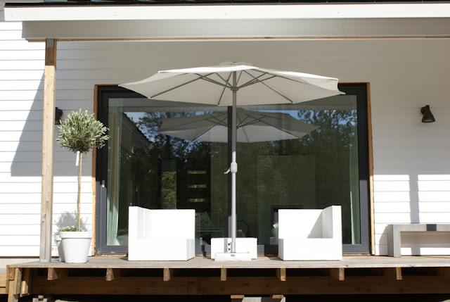 oliivipuu, vinyyliverhous, vinyylitalo, valkoinen varjo, valkoiset kesäkukat, lehtikuusi, liukuovii-ikkuna, betonipenkki