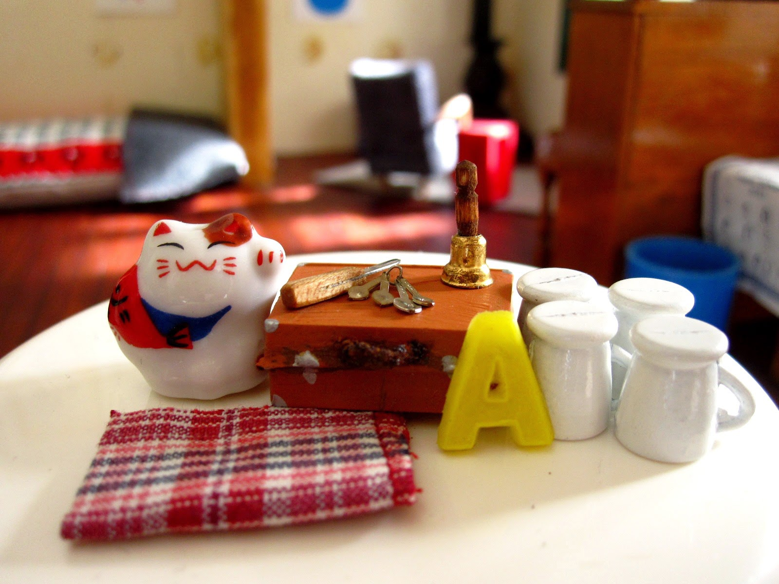 Selection of modern miniature homeware items displayed on a tabletop, including a tea towel, set of mugs, old school case, bell, letter A and cat ornament.