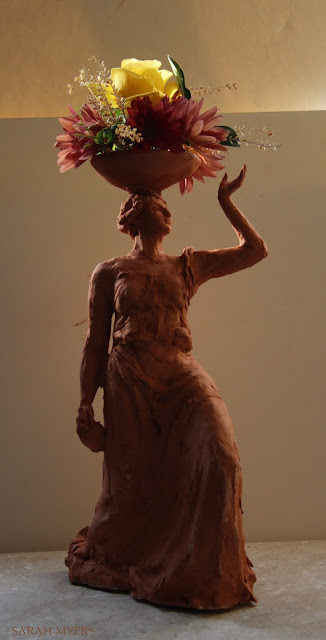 woman, sculpture, bowl, figure, terracotta, ceramic, earthenware, red, Sarah, Myers, flowers, lady, escultura, art, arte, clay, bottle, bouquet, rose, chrysanthemums, mums, yellow, orange, new, artwork, classic, figurative, renaissance, artist, tall, beautiful, spontaneous, kunst, move, walk, stride, arrangement, decor, deco, dark, sunset, light, glow, illumination, lighting