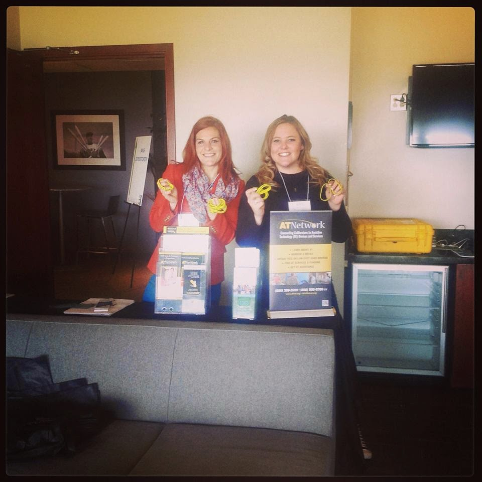 picture of Emily and Rachel setting up an outreach table with AT Network yellow bracelets in their hands