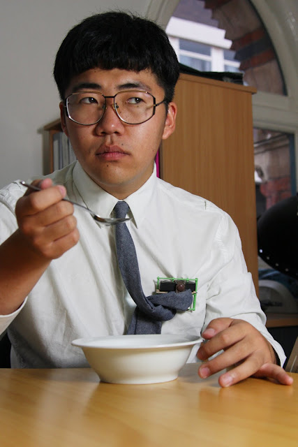 Man eating soup in an office wearing a brooch which holds his tie out of the way.