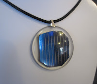 Necklace with circle pendant featuring a blue solar cell