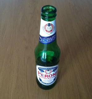 a half full bottle of Peroni Birra