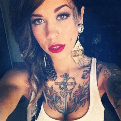 chica morena haciendose un selfie, lleva tatuajes en el pecho