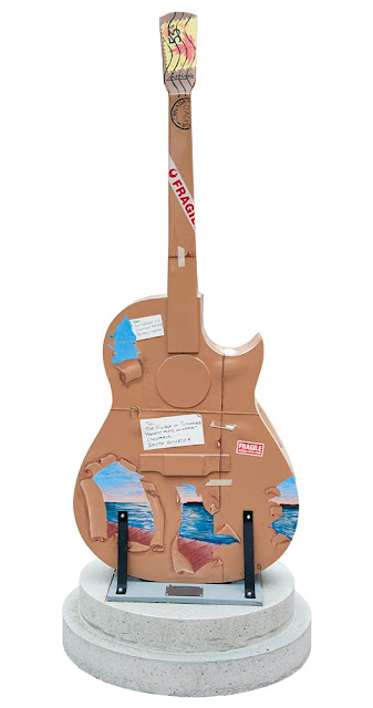 Orillia outdoor art festival featuring large wooden guitars painted by local artists - this guitar is painted to resemble a package being mailed to alaska