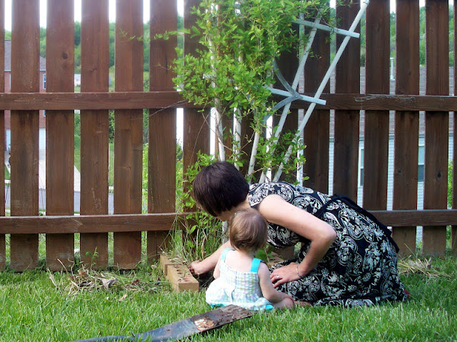 Weeding the plant with baby's help