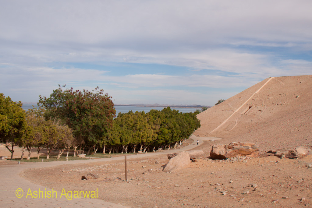 Person walking on the path surrounding the hillocks of the Abu Simbel temple flanked by trees