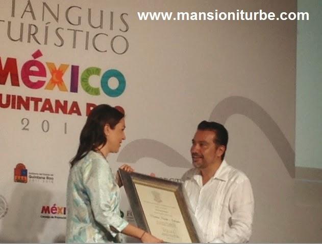 El Secretario Roberto Monroy hace entrega del reconocimiento a la Diseñadora Cristina Pineda