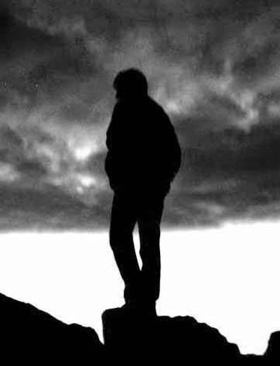 Man standing alone on mountain top picture