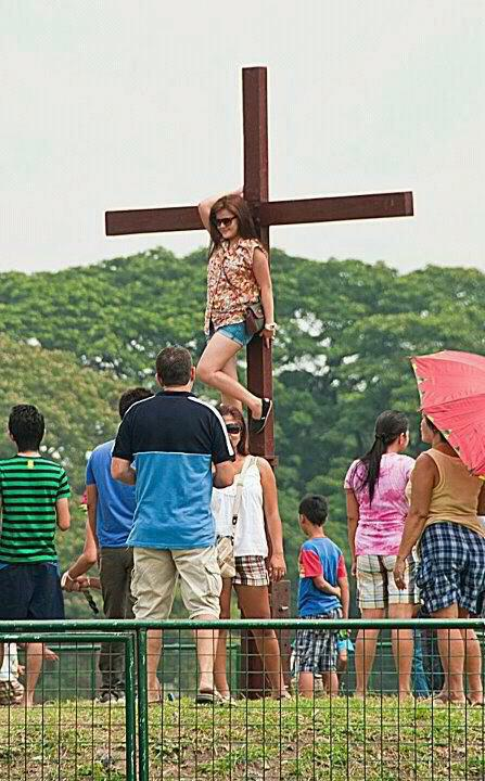 Girl in Sexy Shorts Poses in Front of Cross