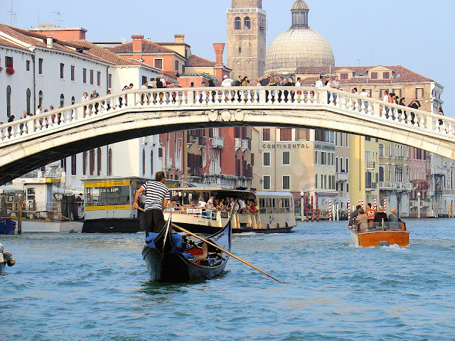A mix of Venetian transportation from the gondola to the private taxi to the vaporetto in the background.
