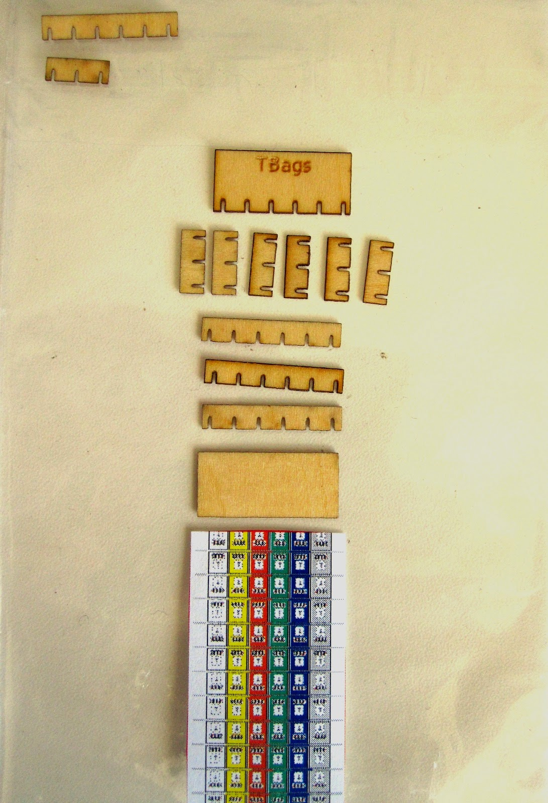 Components of a modern dolls' house miniature tea bag box kit, laid out ready for assembly.