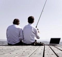 chefe ensinando funcionário a pescar