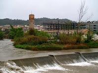 Vista en primer terme de la resclosa de la Fàbrica Vella i al darrere la Torre del Gas o Torre de l'Aigua