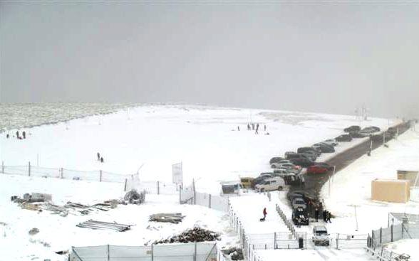 imagen del aparcamiento de la estacion de esqui desde la estacion, vacio y con nieve, con vehiculos tratando de acceder a la estación