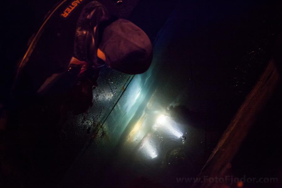 Водолаз заделывает трещину под водой с помощью подводного ножа и пакли