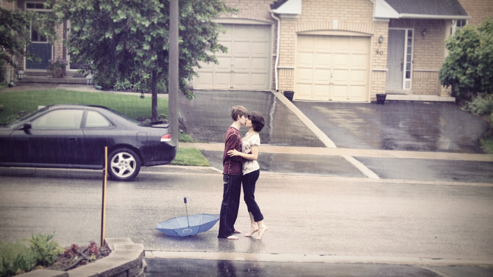 romantic couple in rain - kissing in rain