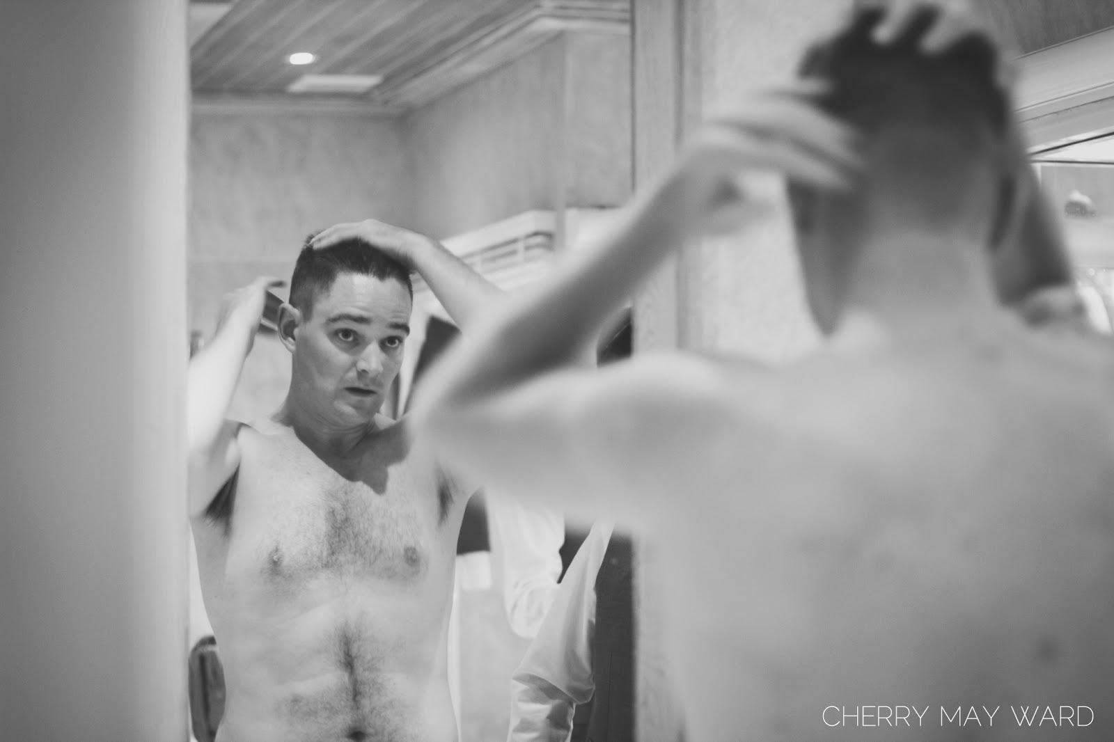 groom getting ready, groom putting gel in his hair, looking into mirror, Koh Samui professional wedding photographer, thailand wedding photos.