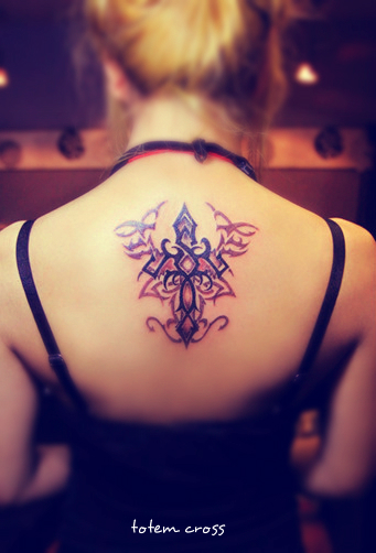 A totem style cross tattoo on the back overlaying with another totem