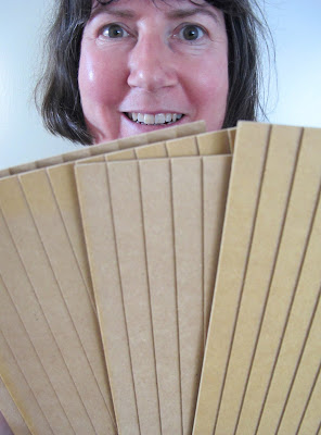 Woman looking happy and holding up four panels of miniature weatherboarding wood.