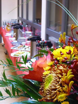 Kaffee- und Kuchentafel hinter herbstlichem Blumenbouquet
