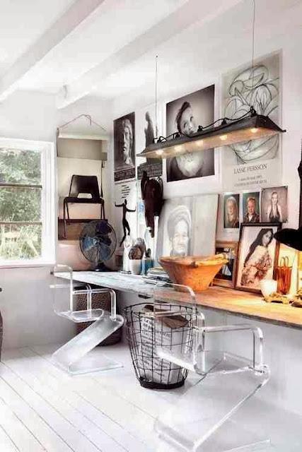 Białe wnętrze, drewniany blat jako biurko, druciany kosz na papiery, ściana pełna inspiracji, przeźroczyste krzesła.