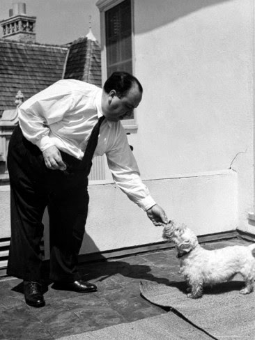Director Alfred Hitchcock standing outside at home feeding his sealyham terrier Mr. Jenkins.