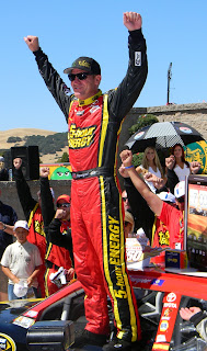 Clint Bowyer stands on his car in Victory Lane