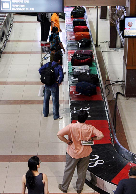 bags on luggage carousel with waiting passengers