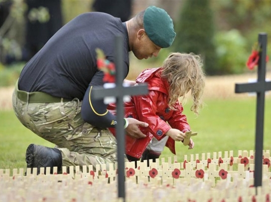 NAMC Montessor Rememberance Veterans Day Activities. Soldier and child place cross.