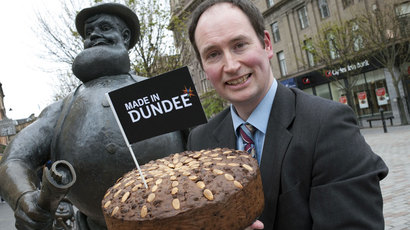 Martin Goodfellow holding a Dundee cake beside the statue of Desperate Dan in Dundee City Centre