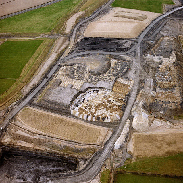Oblique aerial view of Blindwells Opencast Site, Tranent, looking from the east-north-east. Working opencast coal site, in coals of the Limestone Coal Formation, showing various stages in the process. The working face is in the foreground; backfilled spoil in the centre - colours of each load derive from different materials, white and pale brown = sandstone, pale and dark grey = siltstone and shale, dark brown = glacial till overburden; black area = coal storage, pale brown areas = restored overburden. Top left is worked area fully restored to agricultural use. Bottom right is undisturbed ground.