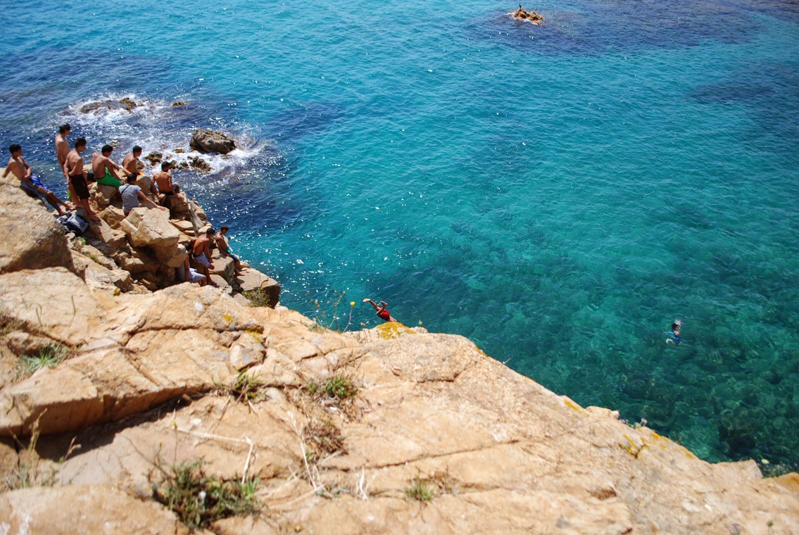 Сверкающие пятками ребята прыгают со скалы в море. Бланес, Коста Брава, Каталония, Испания.