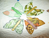 quilt block with four multicolored butterflies made from floral scraps