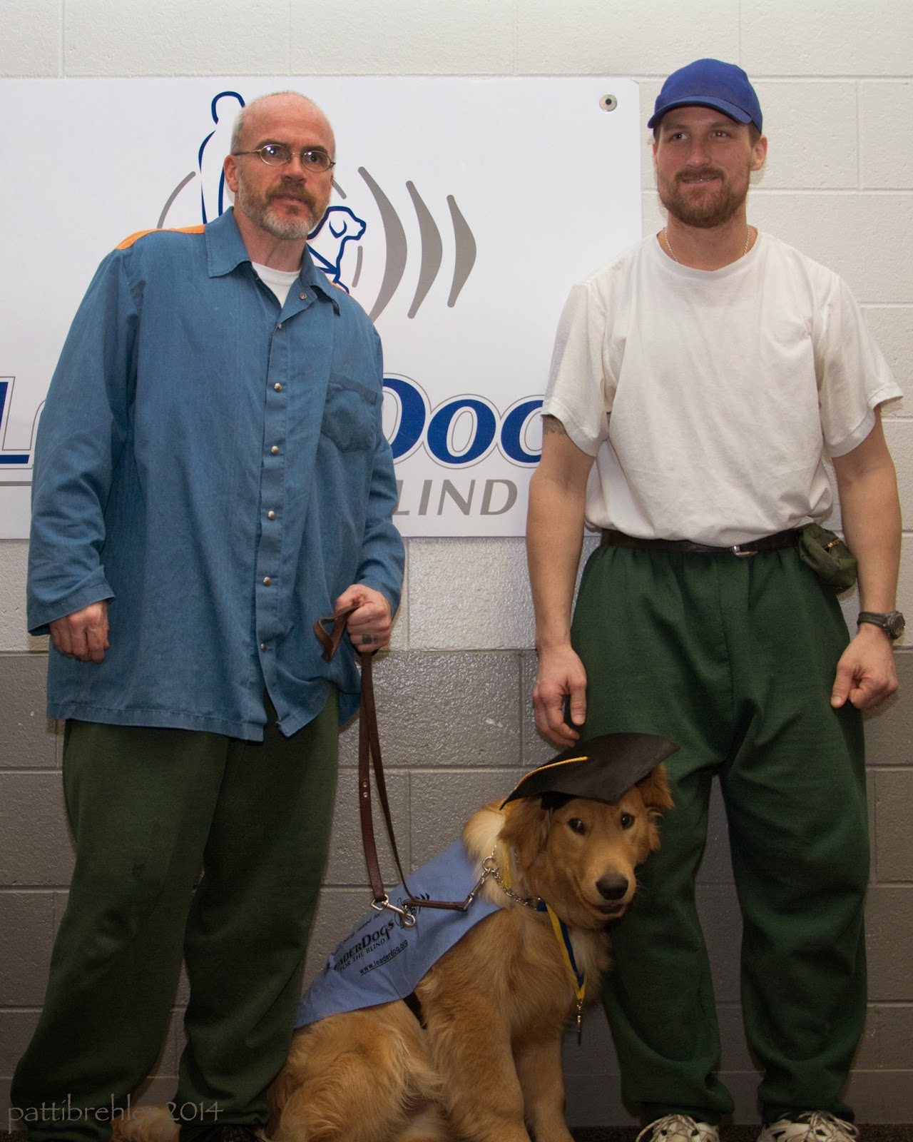 Two men are standing with a golden retriever that is sitting between them. The dog is wearing a baby blue jacket and a black graduation cap and a metal around its neck. The man on the left is wearing a blue longsleeve shirt and green pants. The man on the righ is wearing a white t-shirt, green pants and a blue baseball cap.