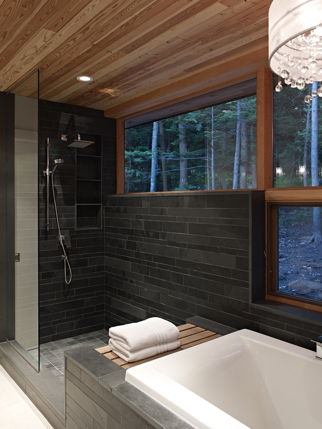 Photo of modern shower cabin with black tiles and wooden window frames in the bathroom