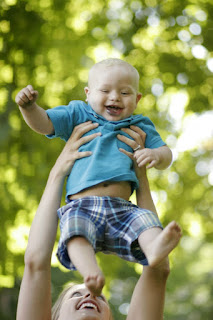 Joyful toddler tossed in the air by mama