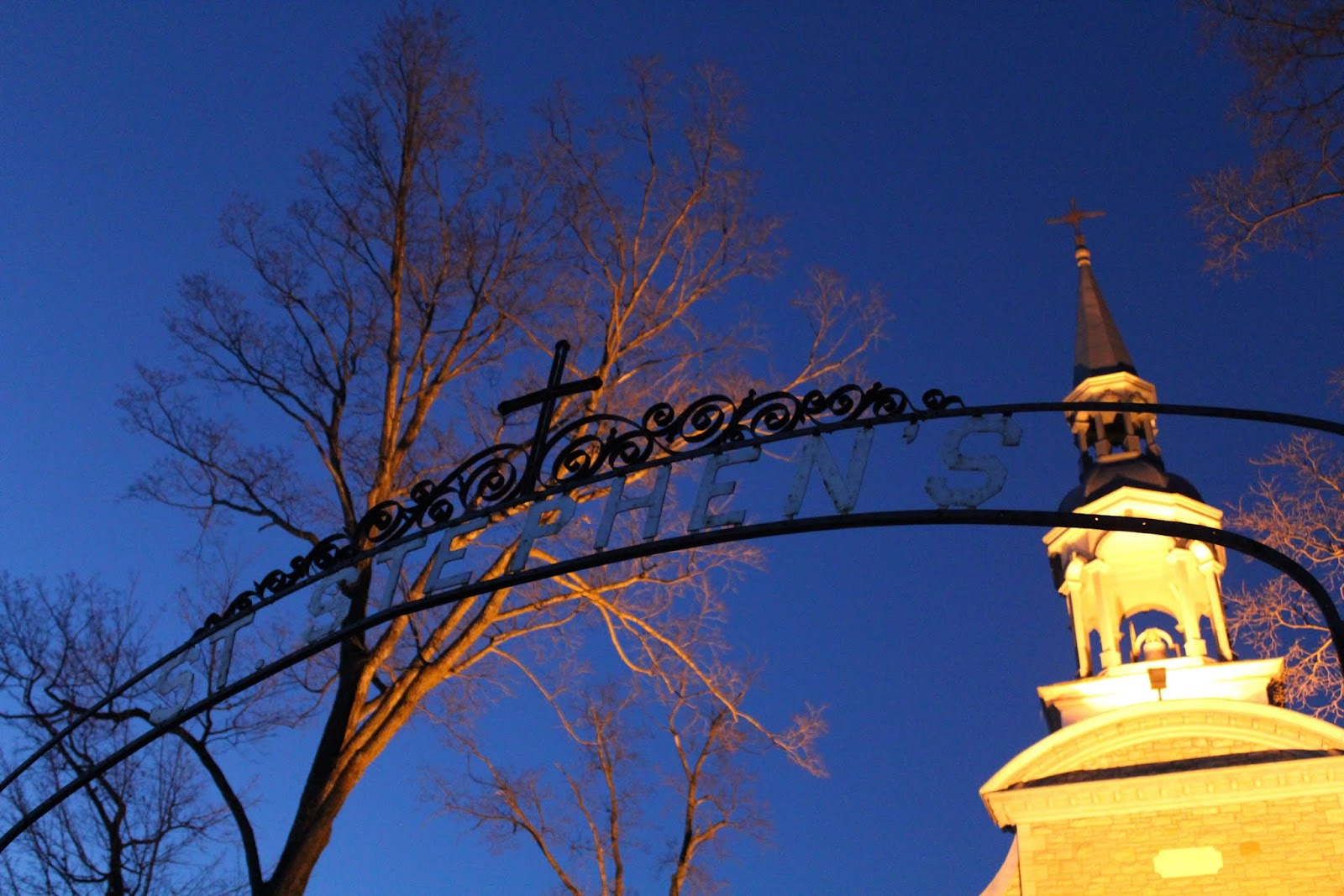 View of Ironwork sign for St. Stephen's silouetted against the crisp winter night sky