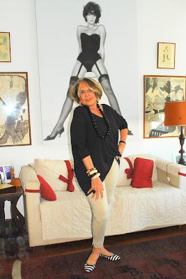 Carmem Verônica em seu apartamento no Leblon. Ao fundo, uma foto ousada do início da carreira.