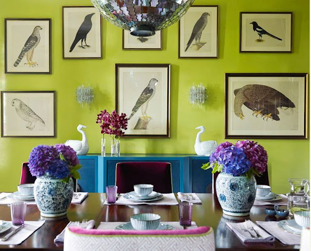 dining room in katie ridde's home with apple green wall with prints of birds, an indigo wall console table, upholstered purple chairs with gold trim, a discoball chandelier and a dark wood table with two Chinese garden pots holding purple hydrangeas