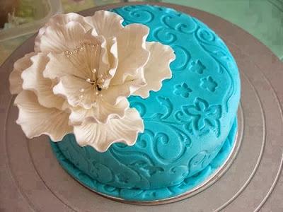 Tarta azul con flor blanca grande