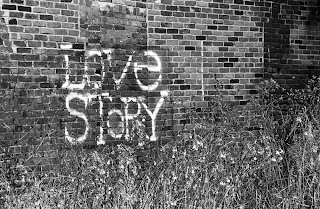 black and white photo of the words 'love story' stenciled on an old brick wall with weeds in front of it