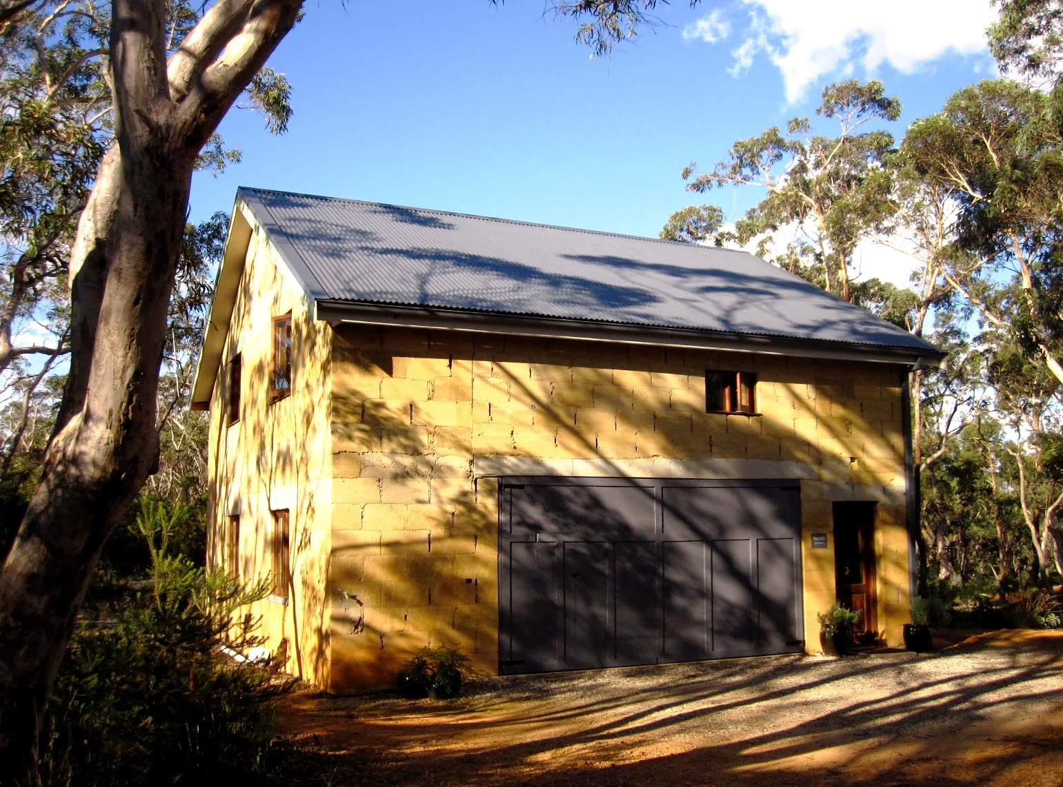 Exterior view of Hat Hill Cottage, a mud-brick cottage