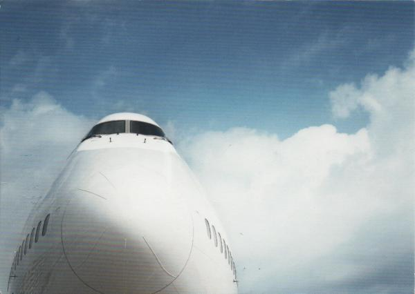 nose of an aircraft against a blue sky with clouds