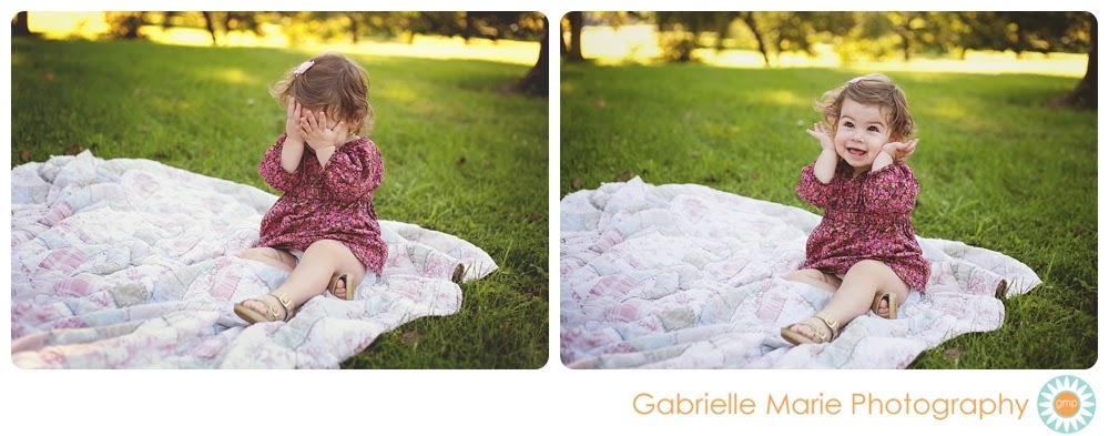 Adorable toddler girl playing peek-a-boo on a quilt in Tower Grove Park.