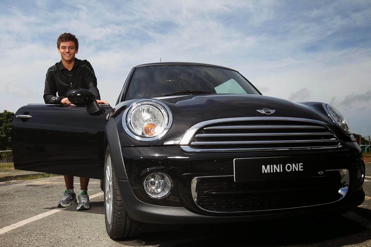 Tom Daley standing by a new black Mini with the door open smiling as he receives it free from Mini