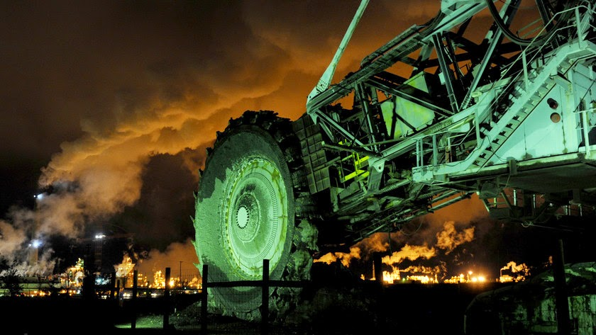A disused mining machine is displayed in front of an oil sands extraction facility near the town of Fort McMurray, Alberta, Canada. (Credit: Mark Ralston/AFP via Getty Images) Click to Enlarge.