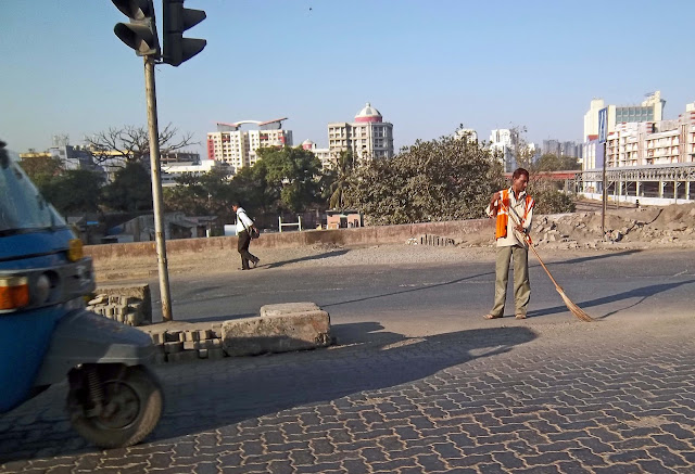 municipal worker sweeping road in reflective jacket