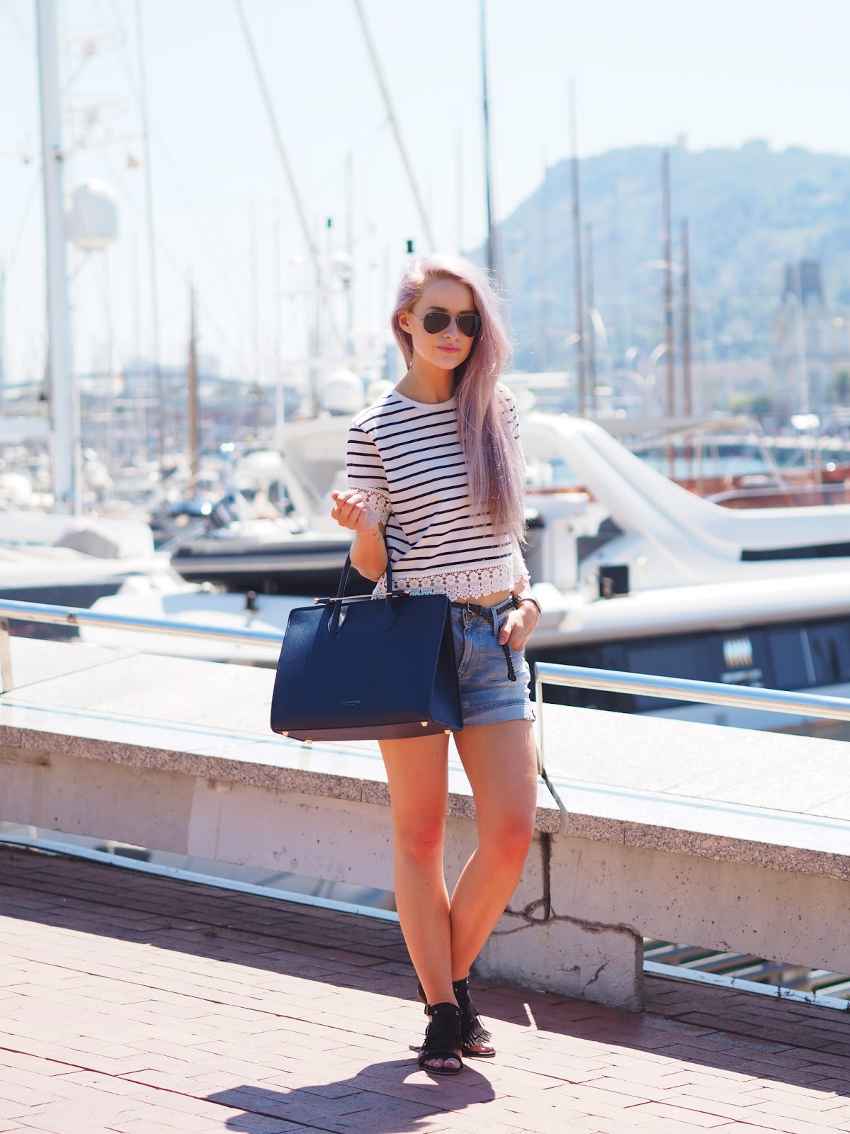 Wearing stripes, denim shorts and black tasseled sandals along the Barcelona Marina